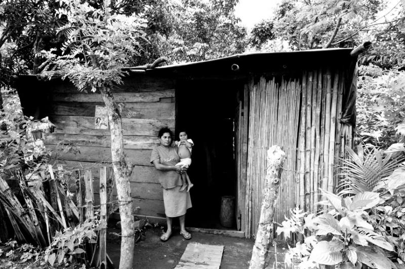 A mother holding her child outside their home made of mud and sticks in rural Nicaragua.
