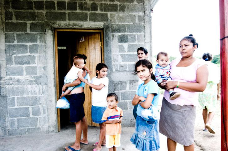 A group gathers outside a new home built for a Nicaraguan family by The Rainbow Network.