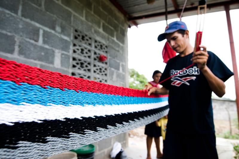 A Nicaraguan man making hammocks, a business that he started after receiving a micro-loan from The R
