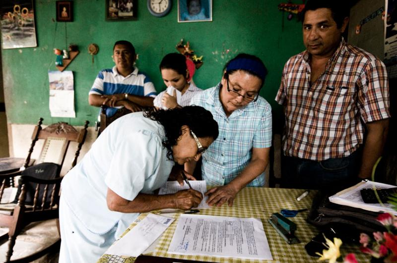 A Nicaraguan woman signs documents after receiving a micro-loan from The Rainbow Network.