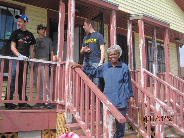Volunteers and the homeowner whose house they helped paint