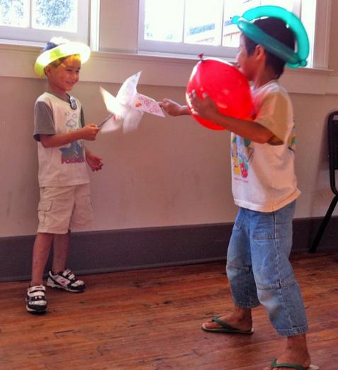 Brothers having fun with their windmills they created at our workshop.