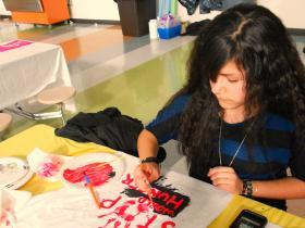 Student painting T-shirt about a global issue she cares about.