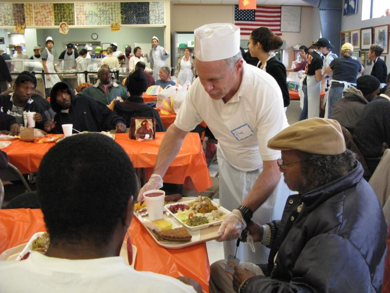 A volunteer delivers a tray of hot, nutritious food to one of our patrons.