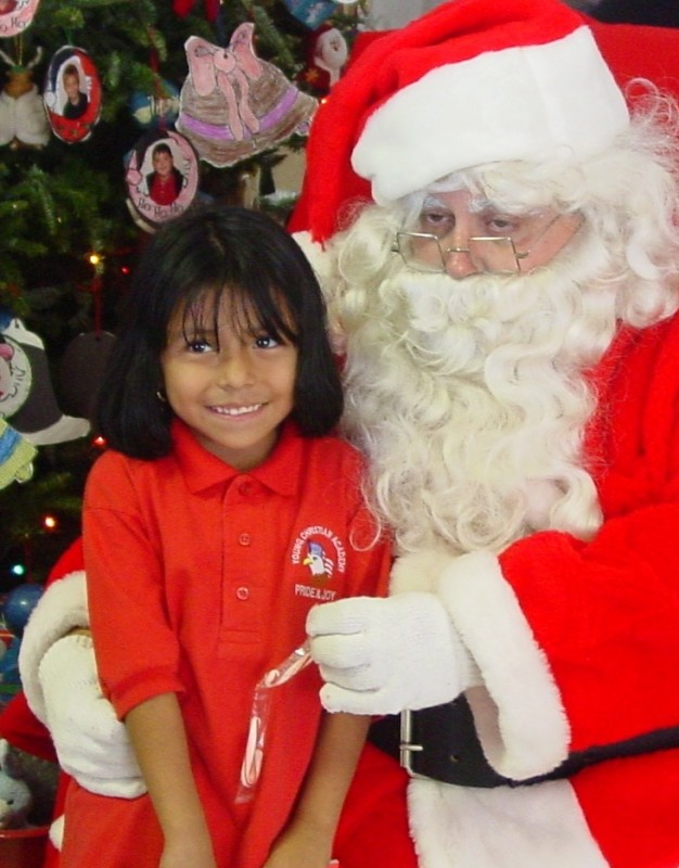 Girl sitting with Santa/ Toy Give Away