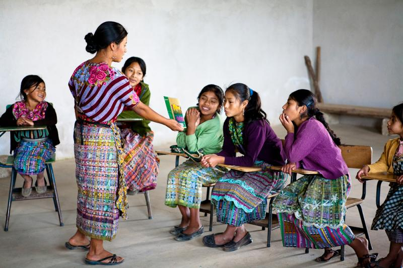 Staff member Hermelinda shares a book with girls from the village of El Llano, Guatemala.
