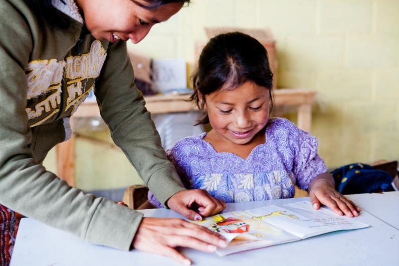 A teacher offers reading support to her student in the village of Tzantinamit, Guatemala.
