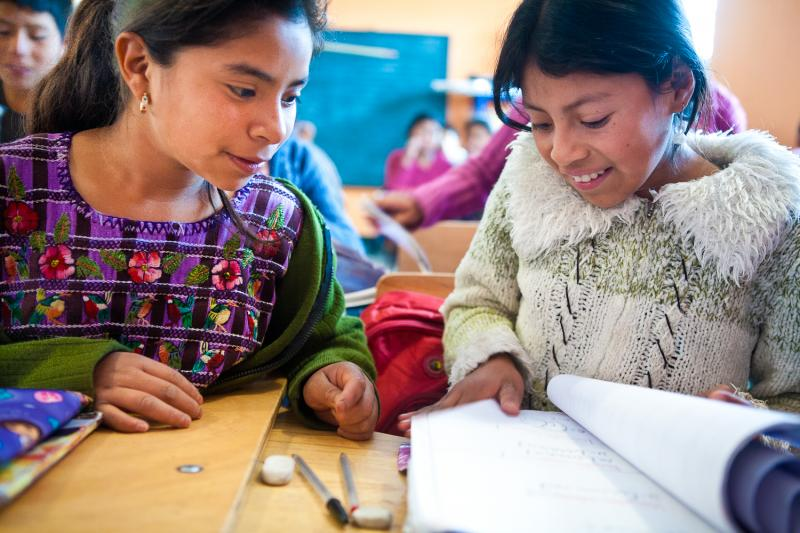 Girls reading donated books in the village of Las Canoas, Guatemala.