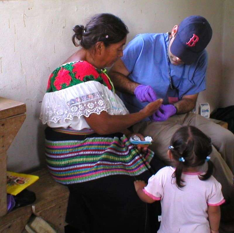 A volunteer checks a patient's blood sugar at an outreach event near Palenque, Chiapas