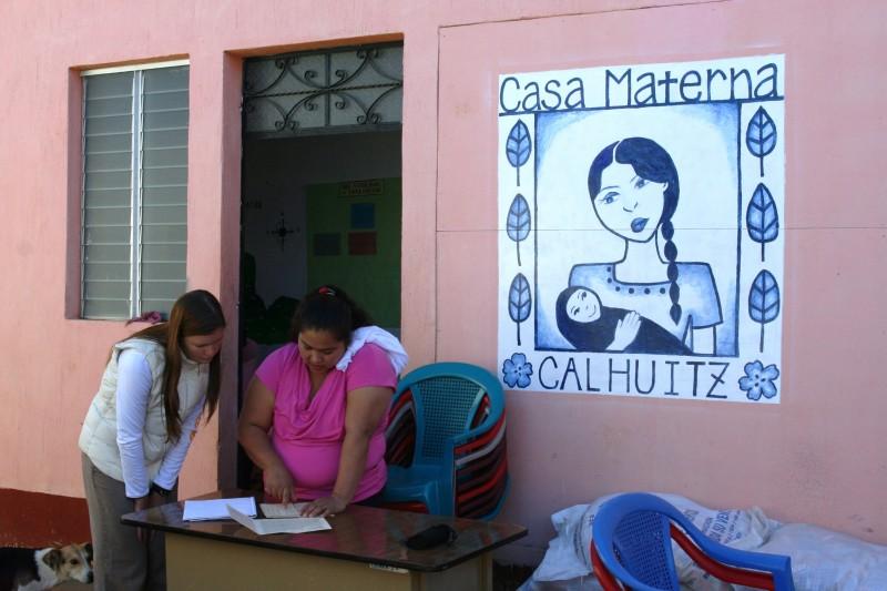 Curamericas staff members reviews health statistics with Nurse Alma in Guatemala