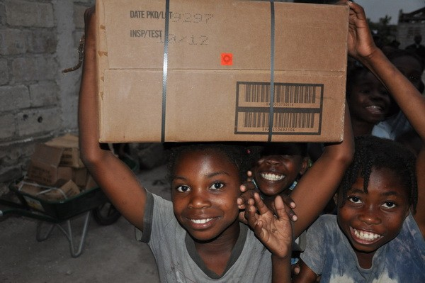Orphans in Haiti help carry relief supplies
