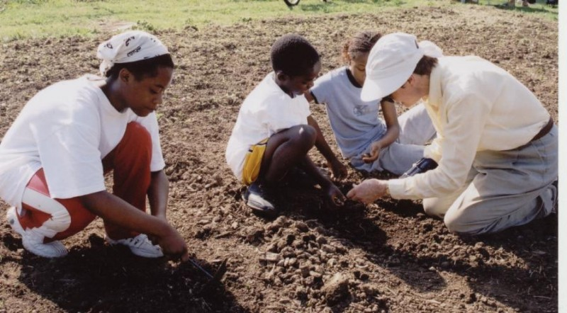 Volunteers help the kids learn how to plant vegetables in the community garden