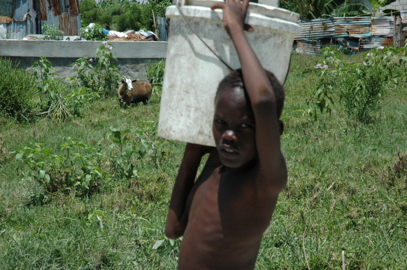 Little boy carrying a 40lbs bucket of water across town