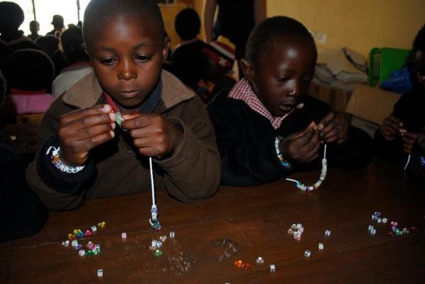 SOHO orphan preschool students learning to make bracelts