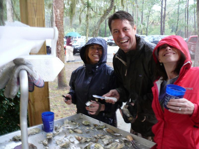 Three members enjoying fresh oysters at our Oyster Roast down in Savannah in March
