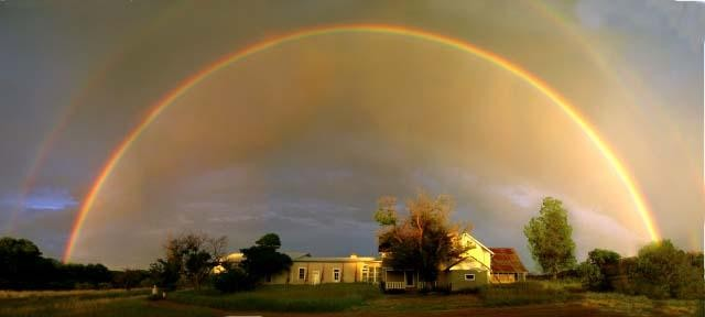 The Empire Ranch House illuminated under an early morning rainbow