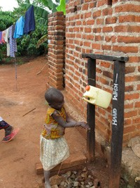 Using a tippy-tap to wash hands in Uganda.