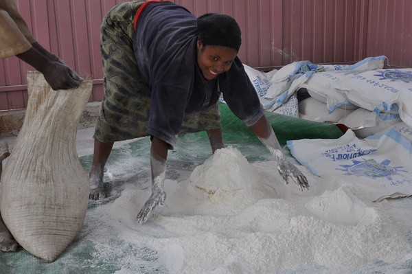 Woman gathering flour at one of ICA's feedings
